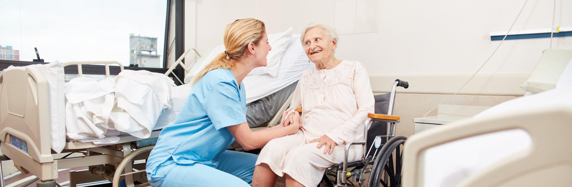 Krankenschwester kümmert sich fürsorglich um behinderte Seniorin im Rollstuhl